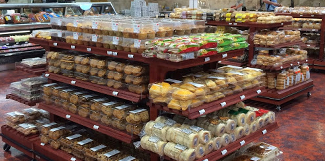 Bakery display in grocery store, featuring a shelving island with center section and endcaps with shelves for packaged baked goods and breads.