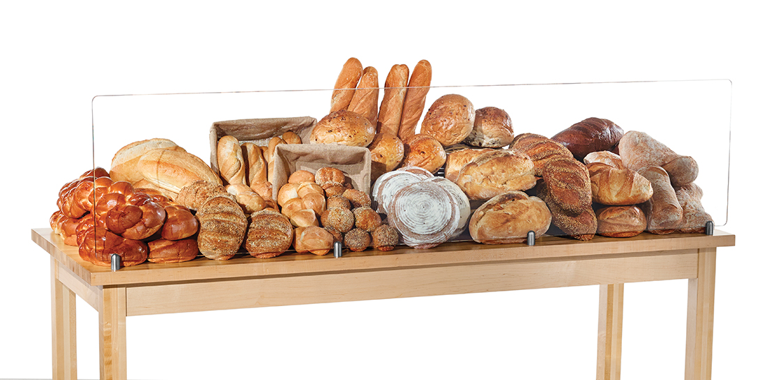 Grocery or bakery bread bar display table with protective glass showcasing French bread, baguettes, rolls, bagels.