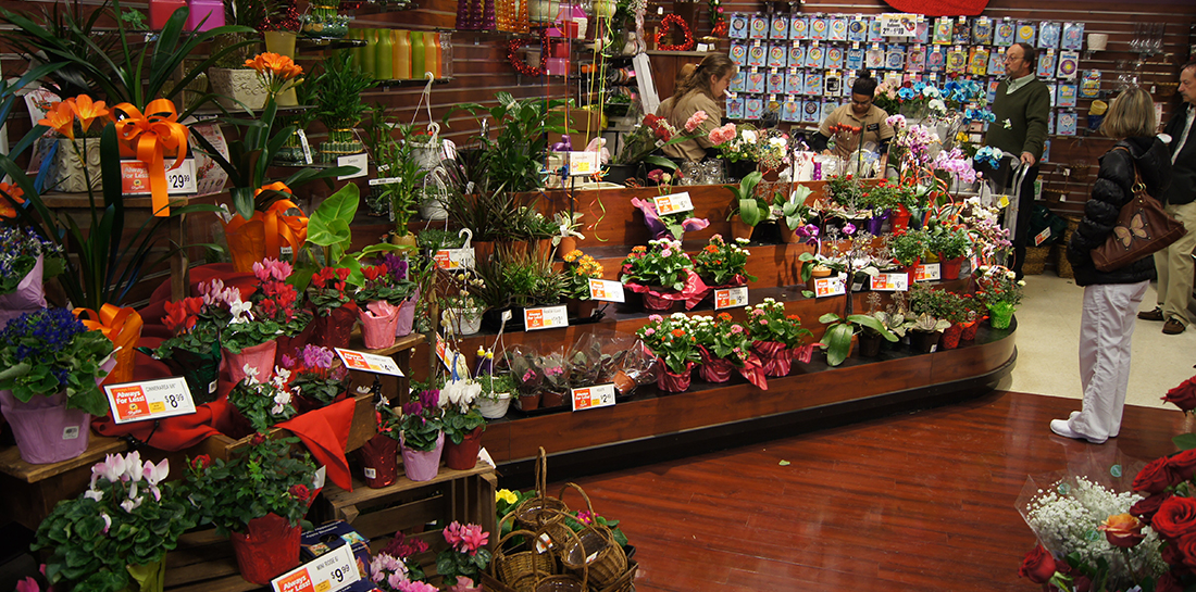 Floral department display for grocery store, featuring work station/wrap stand with tiered shelves on front for merchandising.