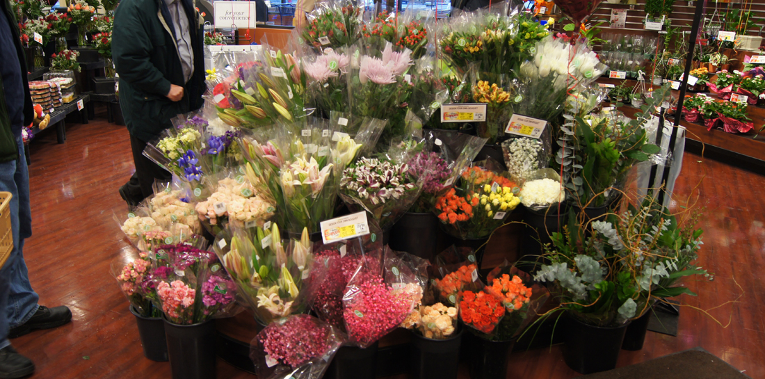 Freestanding floral display for grocery store, with tiered shelves to showcase grab-and-go bouquets and cut flowers.
