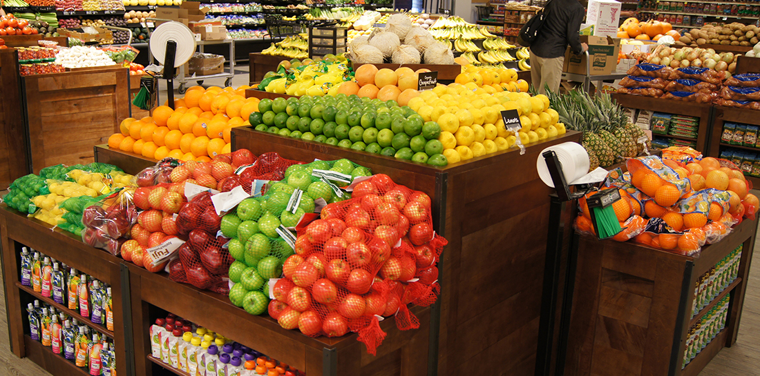 Grocery store island-style produce display of fruits and vegetables with a variety of orchard bins, some with shelves for merchandising packaged goods.