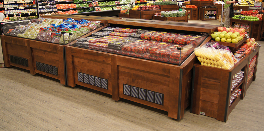 Refrigerated produce display cases for showcasing berries and grapes in a grocery store.