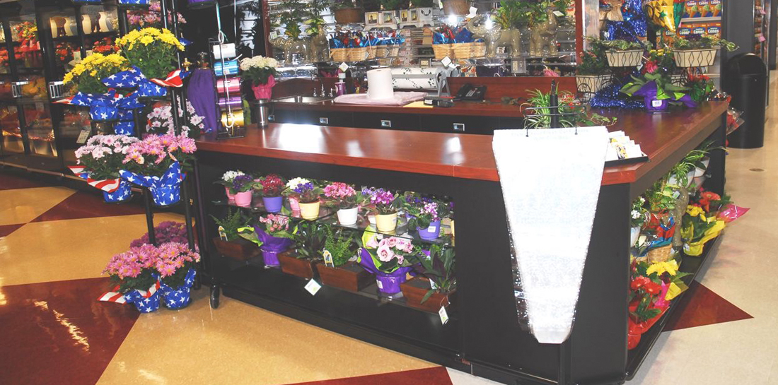 Floral department work station/wrap stand in a grocery store, featuring display shelves on each side for showcasing flowers and gifts.