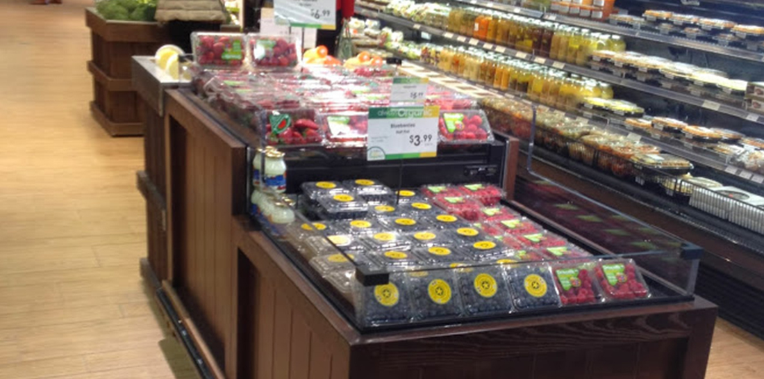 Refrigerated two-level produce display case for showcasing berries in a grocery store.