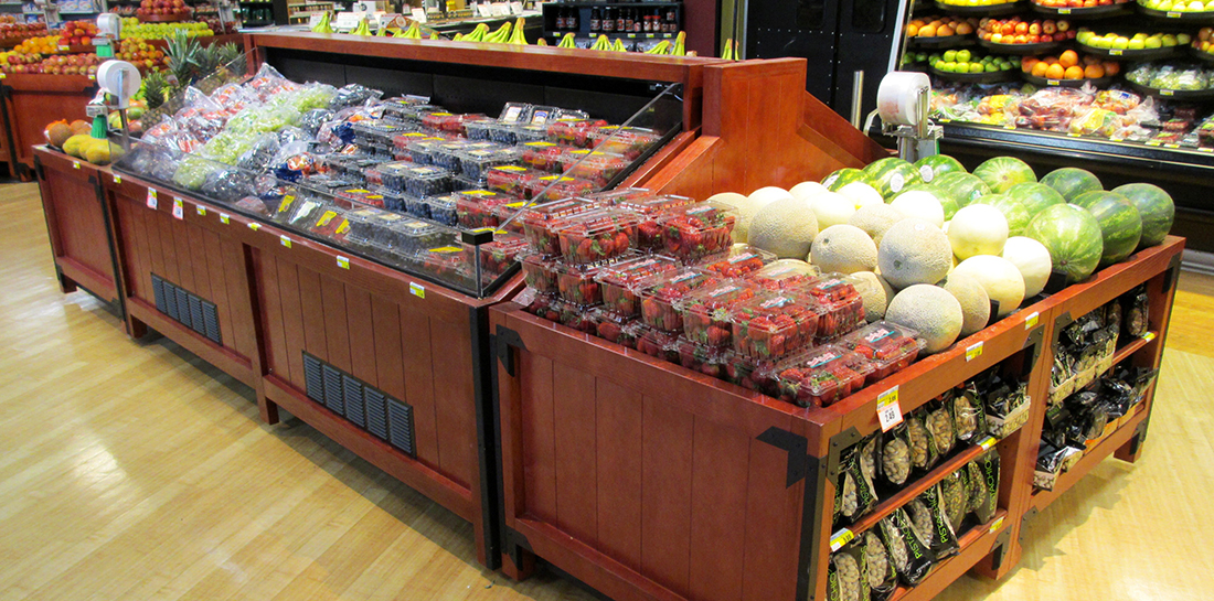 Refrigerated produce display case for showcasing berries and grapes in a grocery store.
