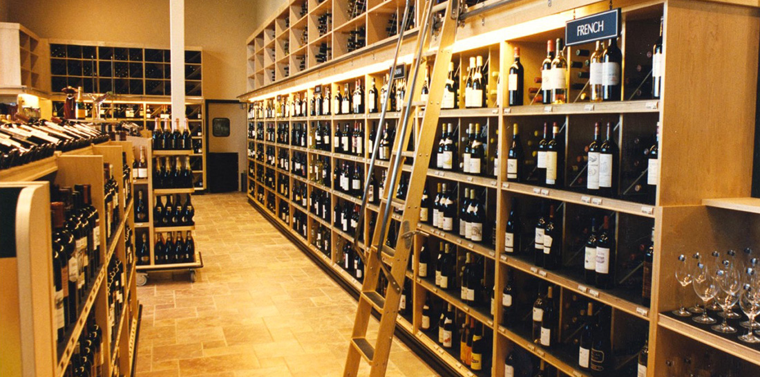 Wine displays for use in grocery stores, liquor stores, package stores or wine shops, featuring a wall display with shelves and bins, as well as shelf units with endcaps.
