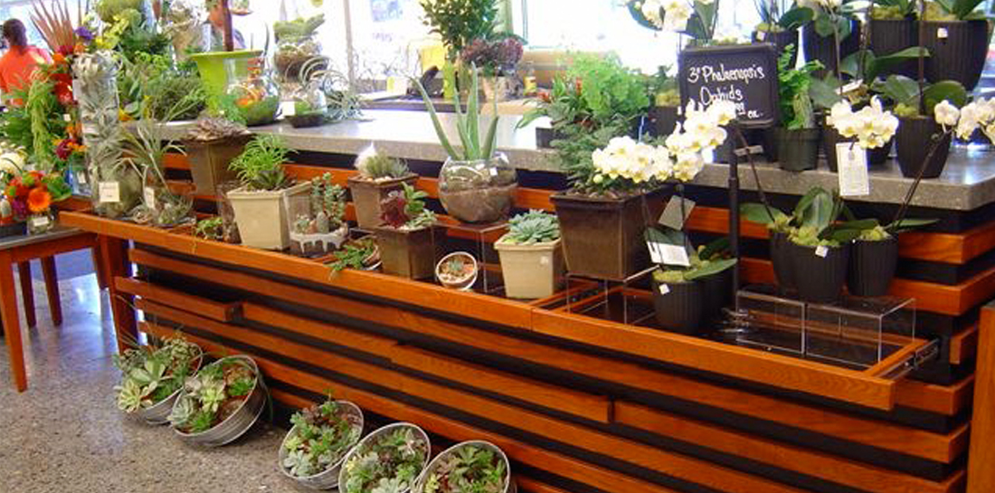 Floral department display for grocery store, featuring work station/wrap stand with shelves on front and endcap for merchandising plants, flowers and gifts.