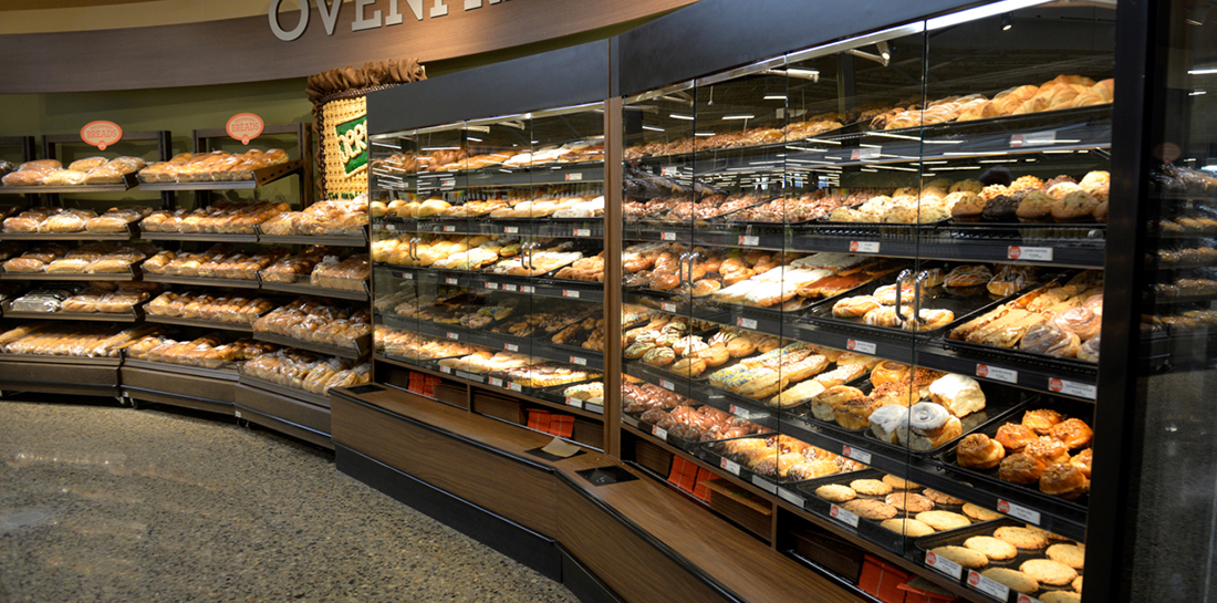 Pastry wall case for a grocery store or bakery, displaying bulk pastry and bread products behind glass doors with dispensers for wax paper and bags or boxes. Shelf fixtures for packaged products complete the wall display.