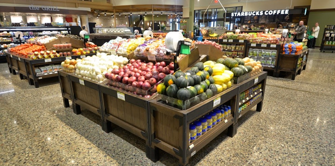 Grocery store produce display of fruits and vegetables in slant bins with orchard bins as end caps with shelves for merchandising packaged goods.
