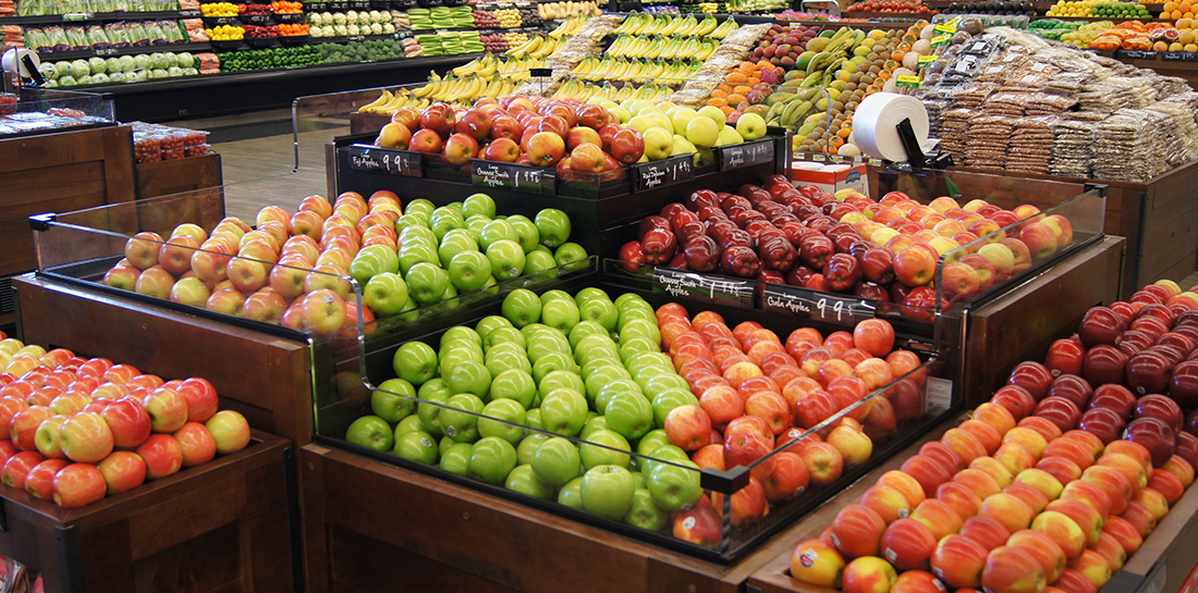 Grocery store island-style produce display of fruits and vegetables with a variety of orchard bins, some with shelves for merchandising packaged goods. Some feature plexiglass sides to hold produce in place, yet keep it visible to customers.