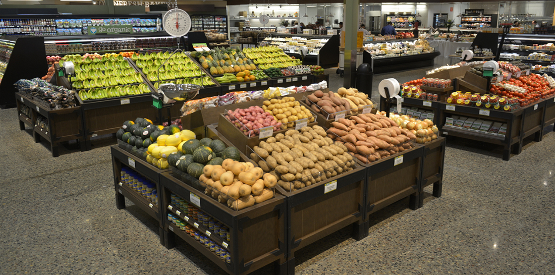 Grocery store produce display of fruits and vegetables with a variety of orchard bins, some with shelves for merchandising packaged goods.