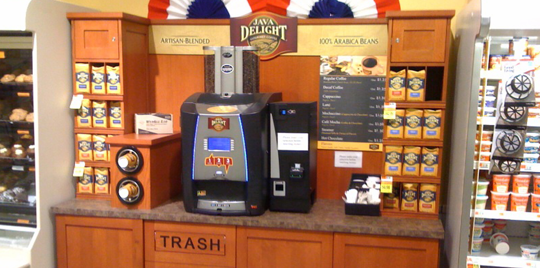 Self-serve coffee bar in a grocery store, featuring storage cabinets, cup dispensers, trash container, merchandising shelves and area for customers to make a cup of gourmet coffee.