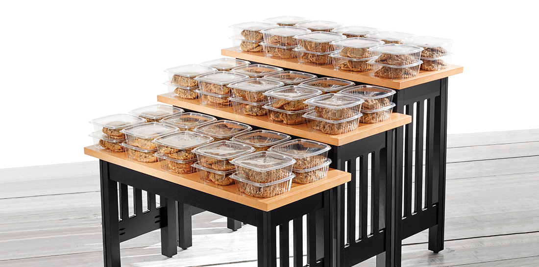 Set of three display tables in graduated heights for merchandising baked goods or other grocery products.