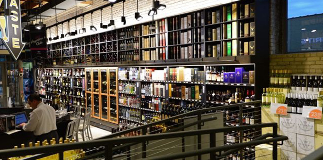 Wine wall display case that showcases wine on shelves, in bins and in locking cabinets, designed for use in grocery stores, liquor stores, package stores or wine shops.