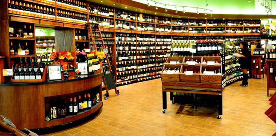 Wine displays for use in grocery stores, liquor stores, package stores or wine shops, featuring a wall display with shelves, shelf units with endcaps and a tasting bar with display area.